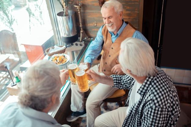 Cerveza en pub. vista superior de jubilados canosos alegres comiendo y bebiendo cerveza en el pub