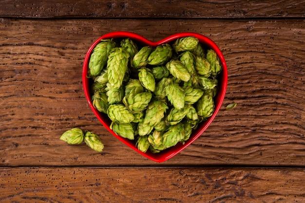 Cerveza que elabora los ingredientes conos de lúpulo en cuenco rojo del corazón en fondo de madera. concepto de cervecería de cerveza.