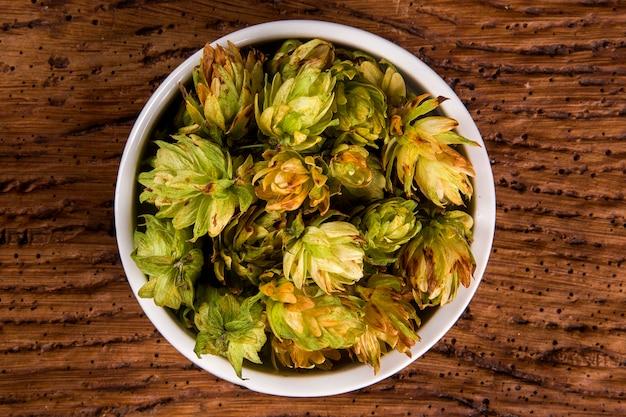 Cerveza que elabora los ingredientes conos de lúpulo en el tazón de fuente blanco en fondo de madera. concepto de cervecería de cerveza.