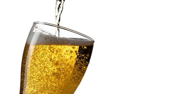 Cerveza que vierte en el vidrio aislado en el fondo blanco