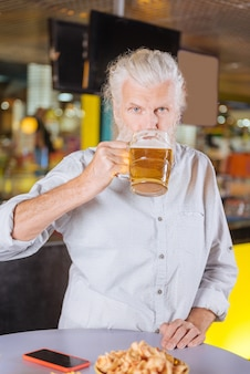 Cerveza sabrosa. hombre alegre encantado de beber alcohol mientras descansa en el pub