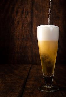 Cerveza servida en vaso con fondo de madera rústica.