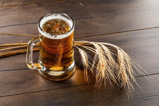 Cerveza en una taza de vidrio con espigas de alto ángulo de visión sobre una mesa de madera