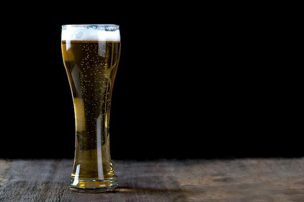 Cerveza en vaso sobre la mesa de madera y fondo negro.