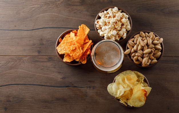 Cerveza en un vaso con vista superior de snack en una mesa de madera