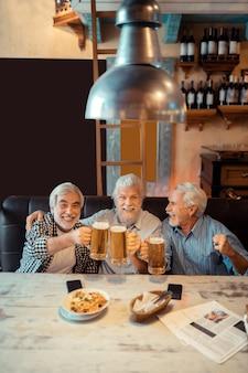 Cerveza tras victoria. jubilados alegres bebiendo cerveza después de la victoria de su equipo de fútbol