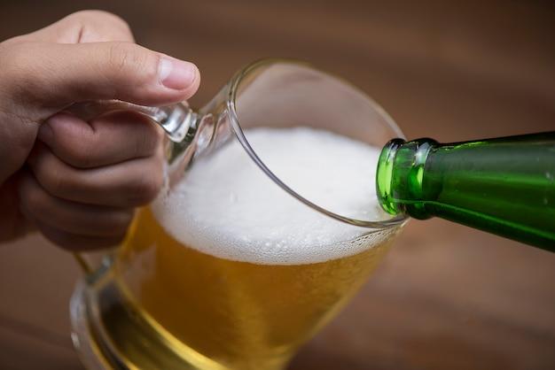 Cerveza se vierte en un vaso de botella