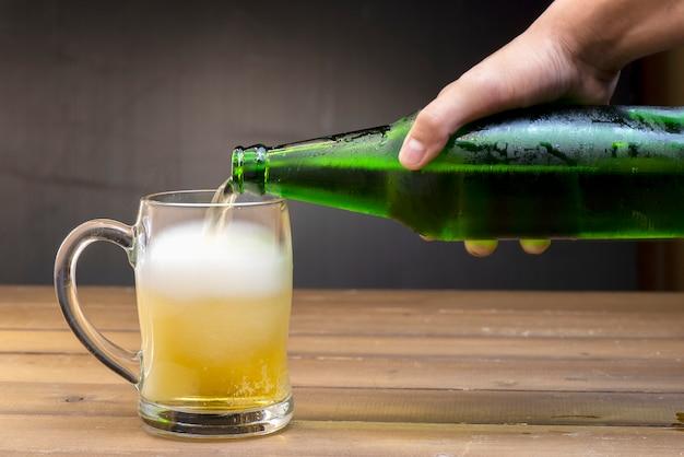 Cerveza se vierte en un vaso por el movimiento de la botella.