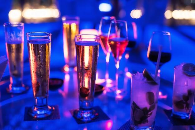 Cerveza, vino, champán, bebida de alcohol espumoso en la mesa del pub y restaurante para un grupo de amigos para pasar el rato y divertirse por la noche.