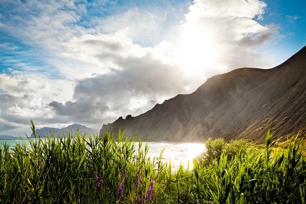 Césped, mar y montaña con cielo nublado