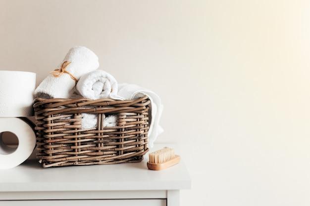 Cesta con accesorios de baño. un juego de toallas enrolladas y dobladas, cepillo para pies y papel higiénico.