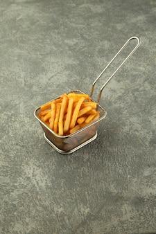 Cesta de acero de papas fritas sobre fondo gris liso