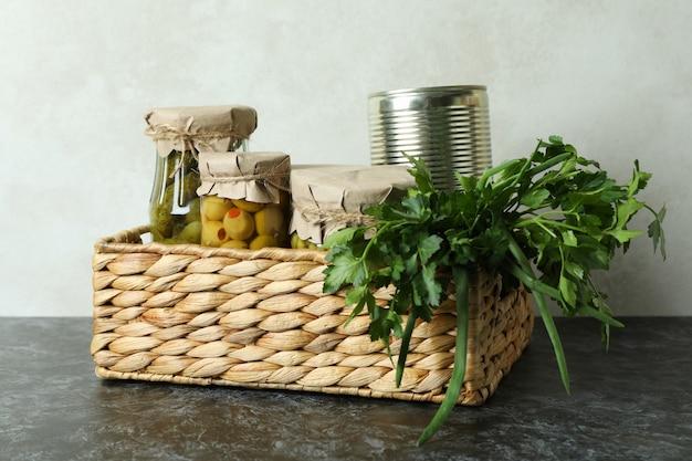 Cesta con alimentos e ingredientes encurtidos en mesa ahumada negra