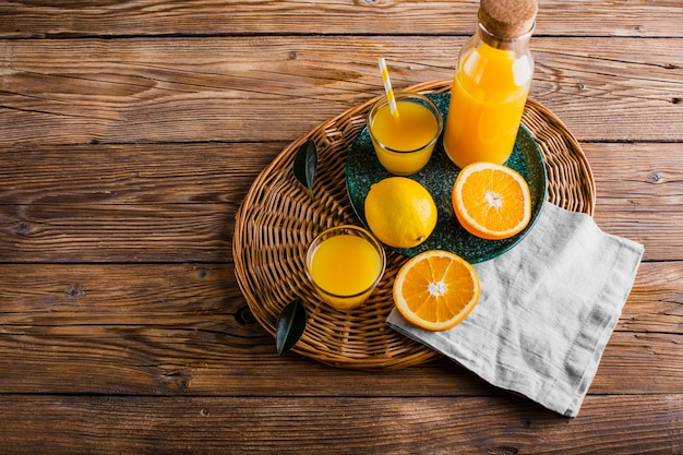 Cesta de alto ángulo con botella y vaso de jugo de naranja
