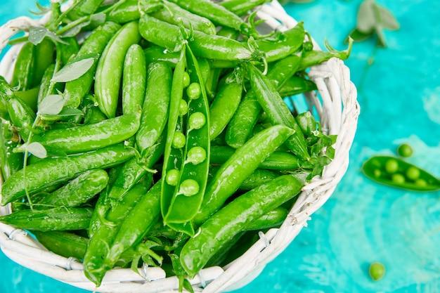 Cesta blanca con guisantes verdes frescos en la mesa azul. concepto de comida vegana y vegetariana. endecha plana.