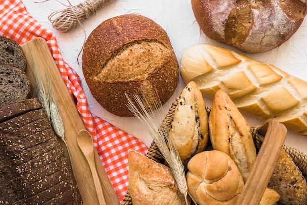 Cesta con bollos cerca de hogazas de pan