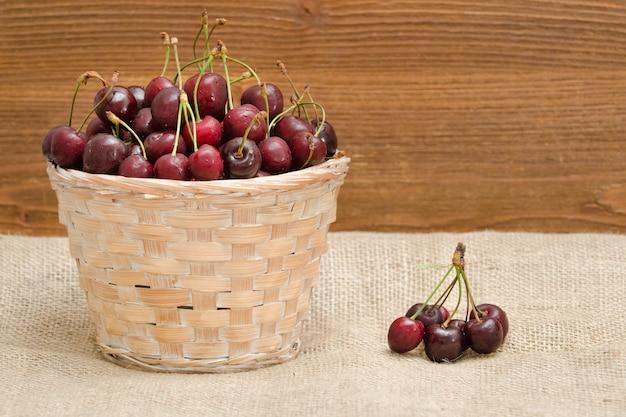 Cesta con cerezas en una mesa de madera. copia espacio