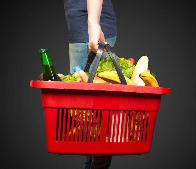 Cesta con comestibles en mano de mujer