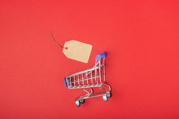 Cesta de la compra y etiqueta con lugar para agregar texto sobre un fondo rojo.