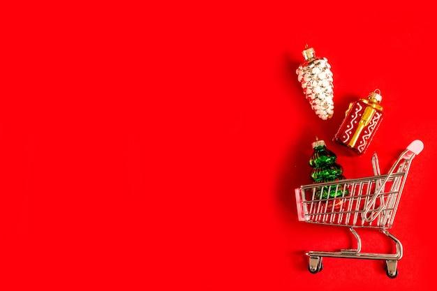 Cesta de la compra llena de vidrio diferente y juguetes de árbol de navidad brillante sobre un fondo rojo.
