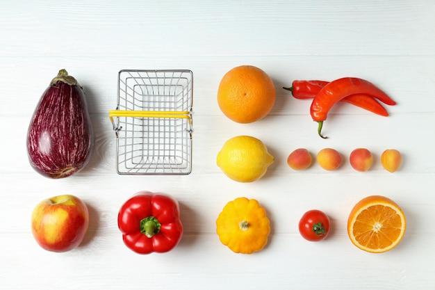 Cesta de la compra, verduras y frutas en la mesa de madera blanca