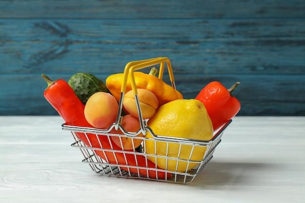 Cesta de la compra con verduras y frutas en la mesa de madera