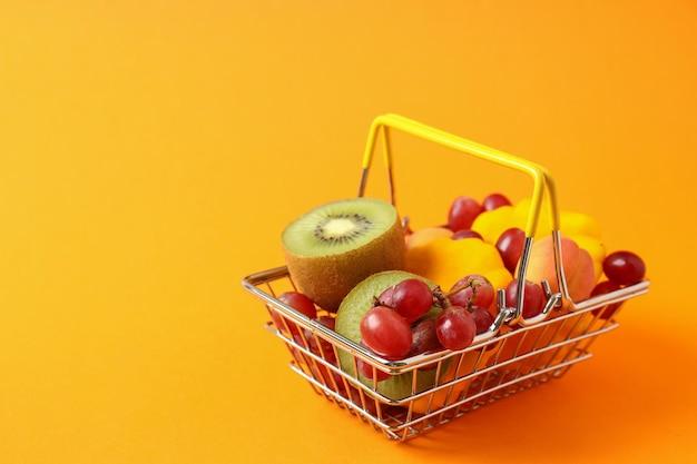 Cesta de la compra con verduras y frutas sobre fondo naranja