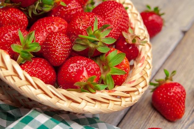 Cesta de la cosecha de fresas en la mesa de madera de cerca
