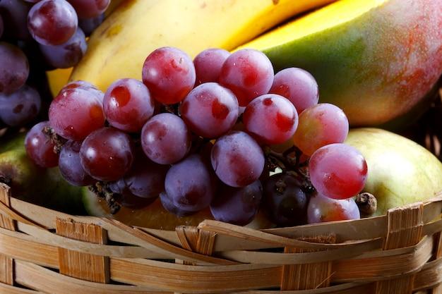 Cesta de frutas en la finca con uva, mango, plátano.