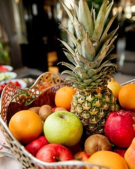 Cesta de frutas con naranjas de piña, kiwi y manzanas