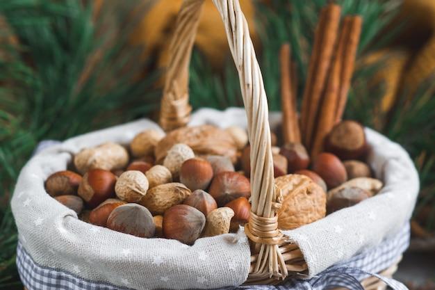Cesta con frutos secos variados cacahuetes nueces avellanas rama de pino manta amarilla acogedor concepto saludable