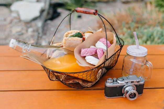Cesta de hierro con botella de jugo de naranja y bocadillos de pie sobre la mesa de madera. foto al aire libre de comida para picnic, vaso vacío y cámara.