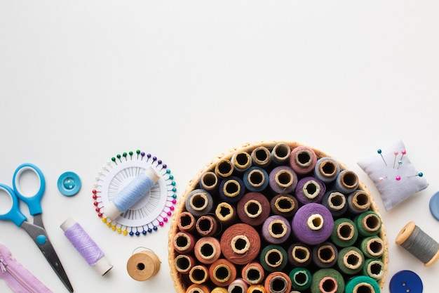 Cesta con hilos de coser y accesorios de costura.