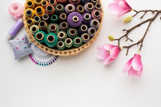 Cesta con hilos de coser y flores de orquídeas naturales.