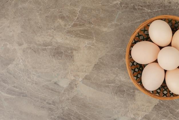 Cesta de huevos blancos sobre mesa de mármol.