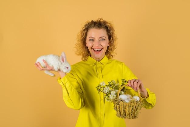 Cesta con huevos huevos cazar huevos de pascua conejito feliz día de pascua lindo conejo peludo mujer sonriente sostiene