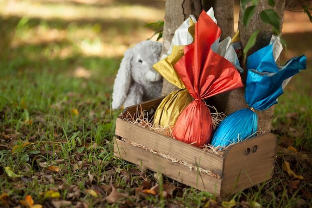 Cesta de huevos de pascua brasileña debajo de un árbol, con un conejito en la pared