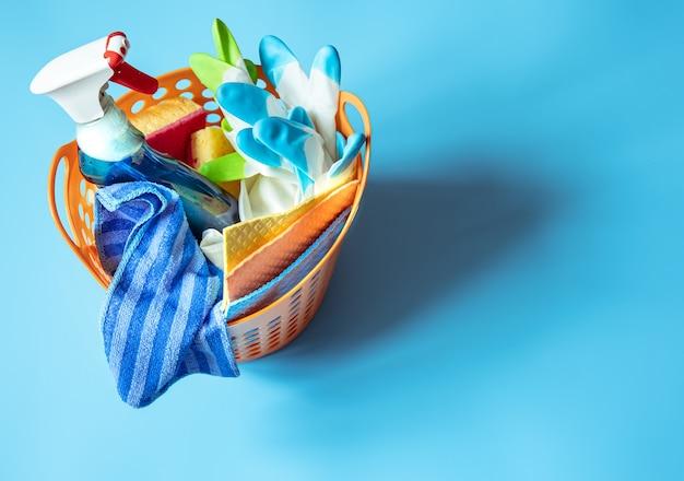 Cesta con un juego de accesorios para la limpieza. fondo de esponjas, trapos, detergente y guantes