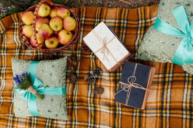 Cesta de libros de manzana, ramo de flores, almohada con cinta en cuadros escoceses