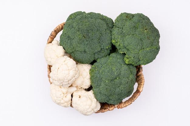 Cesta llena de brócoli y coliflor racimos vista superior sobre superficie blanca