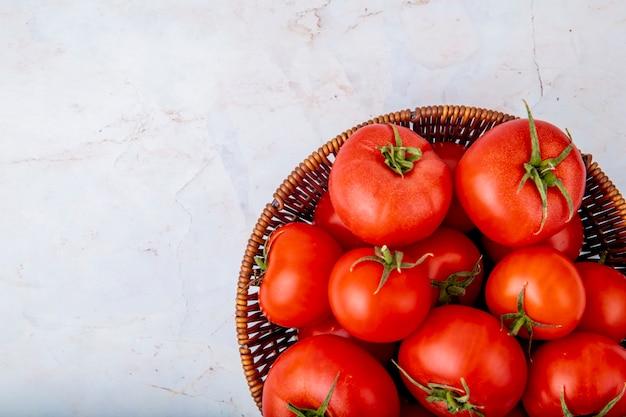 Cesta llena de tomates en superficie blanca