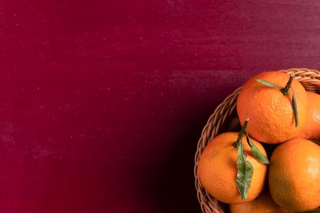 Cesta de mandarinas sobre fondo rojo para año nuevo chino