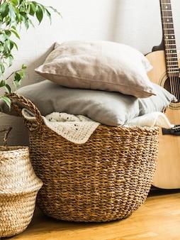 Cesta de mimbre con cojines grises, planta de interior y guitarra en el piso cerca de una pared blanca