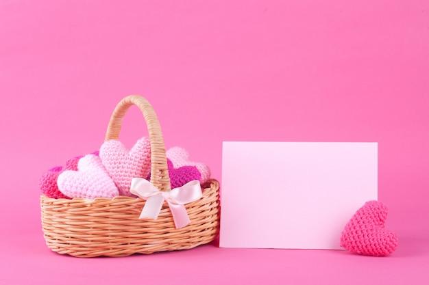 Cesta de mimbre con corazones de punto multicolor. fondo rosa brillante decoración festiva día de san valentín. bricolaje