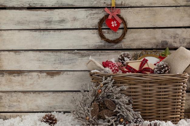 Cesta de mimbre con decoración navideña y nieve falsa