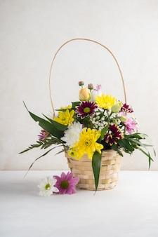 Cesta de mimbre con flores colocadas en el escritorio.