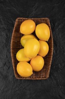 Cesta de mimbre de limones frescos enteros sobre mesa negra.
