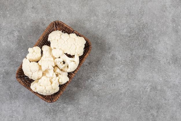 Una cesta de mimbre llena de coliflor fresca madura cortada en trozos pequeños.