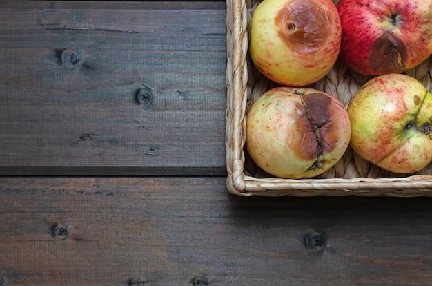 Cesta de mimbre con manzanas feas orgánicas en la mesa de madera. de cerca.