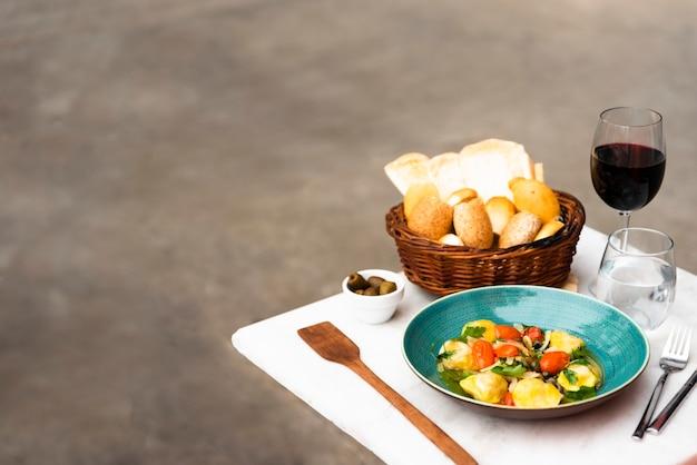 Cesta de mimbre de pan y pasta de ravioles cocidos en mesa blanca